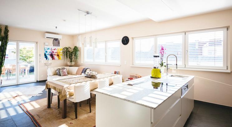 Wohnzimmer mit Essbereich und Kücheninsel in Penthouse