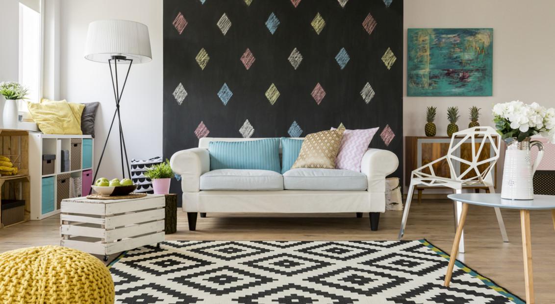 Weißes Sofa mit bunten Kissen in moderner Singlewohnung